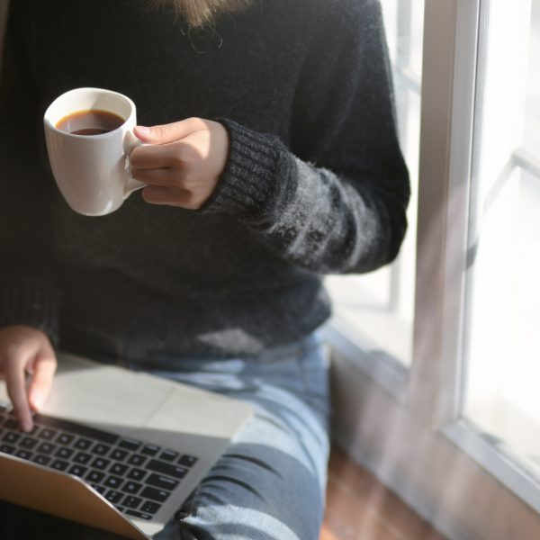 person using laptop drinking coffee
